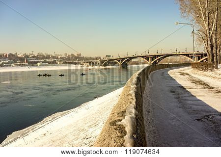 Eastern Siberia, Irkutsk. Angara Pure Water In Winter Day. Old Bridge Over The River, Which Is Const