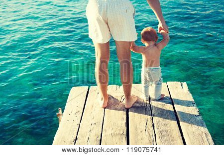 Young Father Holding His Baby Hands by the Sea