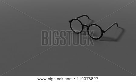 Pair of black round-lens eyeglasses, isolated on grey/black background.