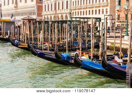 VENICE ITALY - 14TH MARCH 2015: Gondolas docked at the harbour front along Riva degli Schiavoni in Venice during the day.