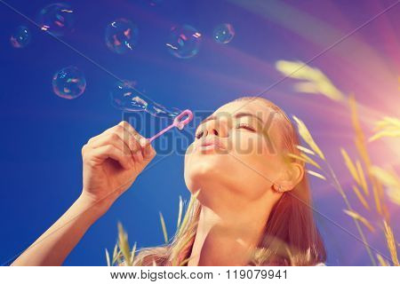 Portrait of pretty woman with pleasure blowing soap bubbles over blue sky background, having fun outdoors in sunny day