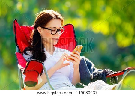 Pretty woman spending time outdoors, sitting in armchair and calling on the phone, enjoying vacation in the camping