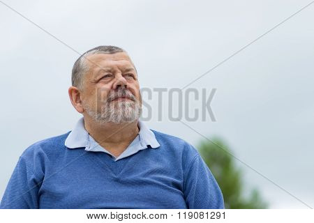 Portrait of a bearded senior man looking up with hope