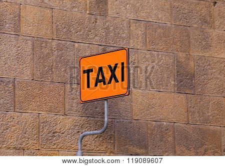 Taxi Sign On The Taxi Stop With A Wall As Background
