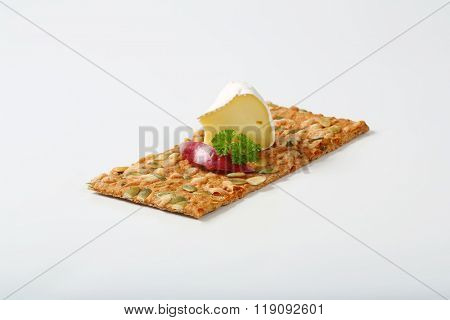 pumpkin seed cracker with white rind cheese and slice of apple on white background