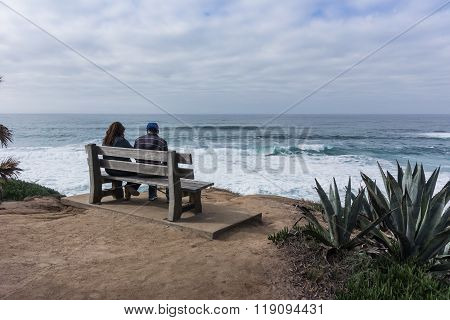 Young Couple Sit On Bench Looking Out Over Ocean