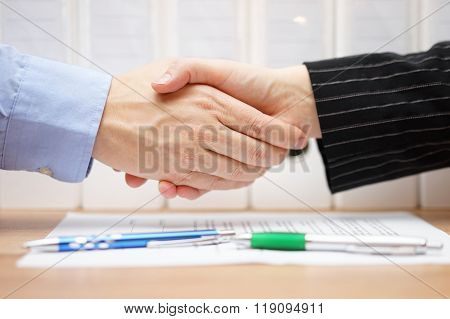 businessman and businesswoman are handshaking over signed contract with binders in background