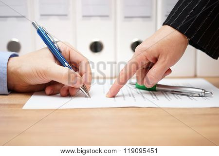 business woman is pointing where to sign on document with documents in background