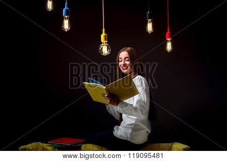 Young creative student with colorful lamps and books