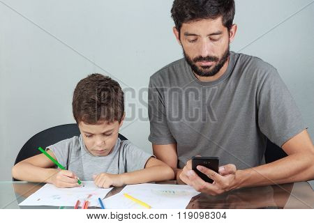 Father Using Smartphone While Your Child Draws With Colored Pencils On The Living Room Table