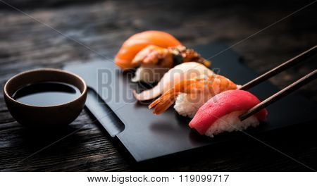 close up of sashimi sushi set with chopsticks and soy