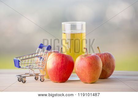apples and apple juice with a shopping cart on a wooden table, outdoor