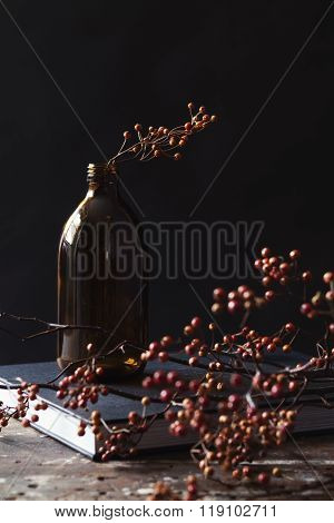 Amber Bottle Vase Of Dried Berry Sticks On Book Table Centerpiece