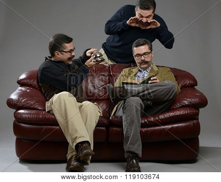 Adult male sitting on sofa and reading  book while others trying to seduce him over gray background.