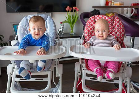 Baby boy and girl twins sitting on the high chair