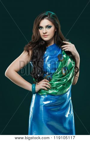 Woman in brilliant blue-green dress with peacock feathers design. Creative fantasy makeup, long dark