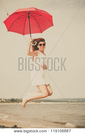 Girl With Red Umbrella On Beach