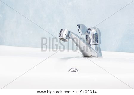 Hand washing basin with grey background in the bathroom. Flowing water.