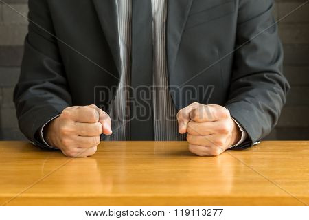 Businessman With Clenched Fist On The Desk