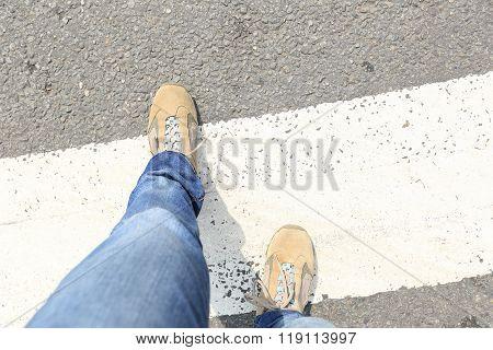 people legs walking on zebra crossing road