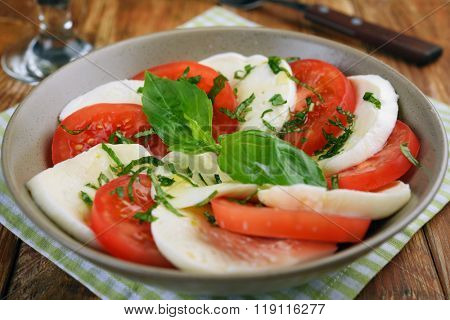 Caprese salad with mozzarella, tomato, and basil leaves. Selective focus on a basil