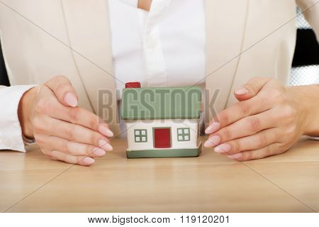 Businesswoman presenting a model house.