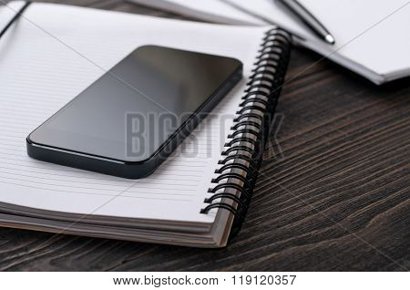 Black Smartphone In The Workplace With Notepad