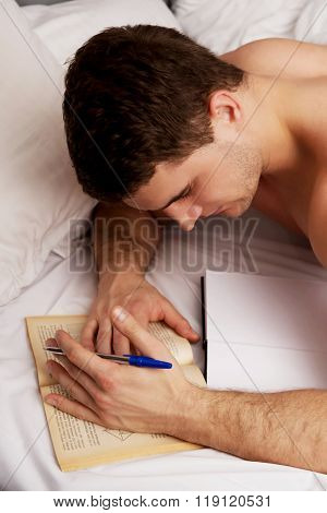 Man learning to exam in his bed.