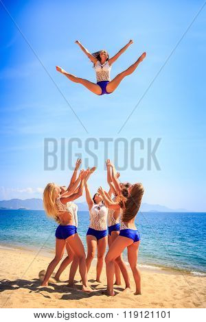 Cheerleaders Perform Toe Touch Basket Toss On Beach