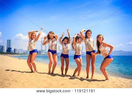Cheerleaders Stand On Beach Laugh Wave Hands Against Azure Sea