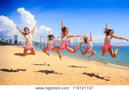 Cheerleaders Jump In Scales At Once On Beach Against Sea