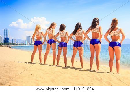 Cheerleaders Stand Backside Hands On Hips On Beach Against Sea