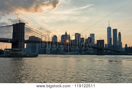 Sunset Over Manhattan Skyline with Brooklyn Bridge in Foreground with View of East River, New York City, New York, USA