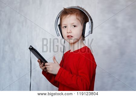 Little Boy With Headset Using Touch Pad, Listening To Music With