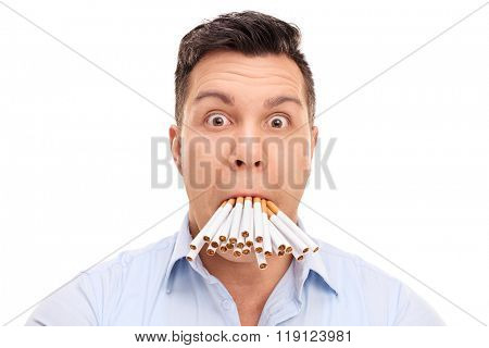 Baffled young man with a bunch of cigarettes in his mouth isolated on white background