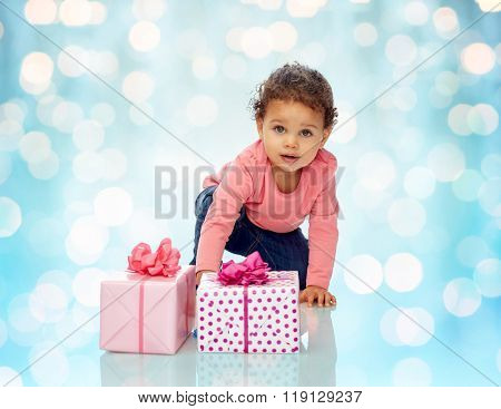 childhood, birthday, holidays and people concept - little african american baby girl with gift boxes and confetti crawling on floor over blue holidays lights background