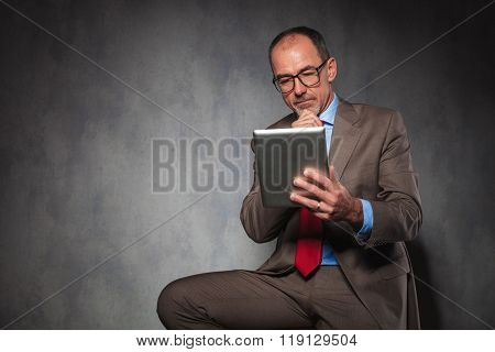 portrait of succesful mature man in suit wearing glasses, thinking and using his tablet while posing seated in studio background