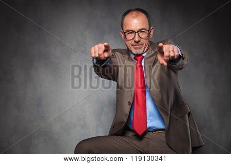 mature elegant businessman wearing glasses, posing seated while pointing both fingers at the camera and smiling in studio background