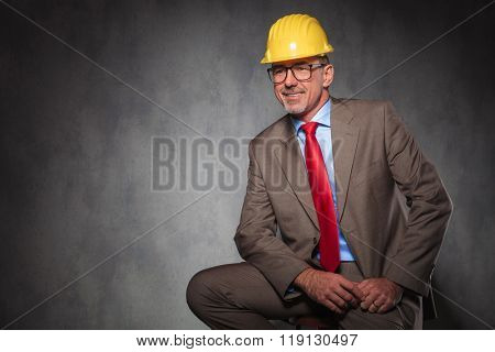 portrait of confident senior engineer wearing helmet and glasses smiling while looking away from the camera in studio background