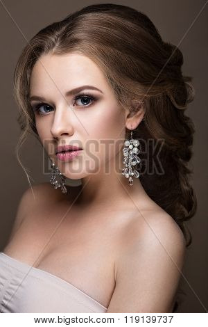 Beautiful blond girl with perfect skin, evening make-up, wedding hairstyle and accessories. Beauty f