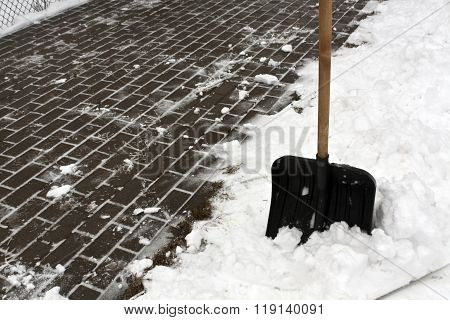 Black Plastic Snow Shovel And Pavement.