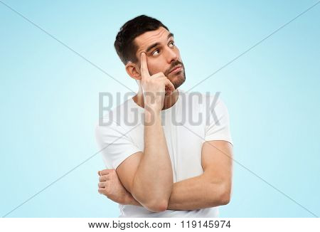 doubt, expression and people concept - man thinking over blue background
