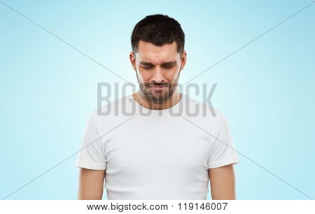 emotion, sadness and people concept - unhappy young man over blue background