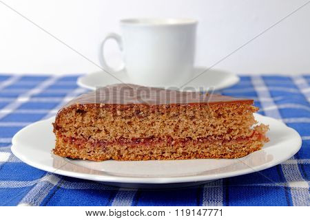 Homemade Gingerbread Topped With Chocolate On A White Plate With Cup Of Coffee