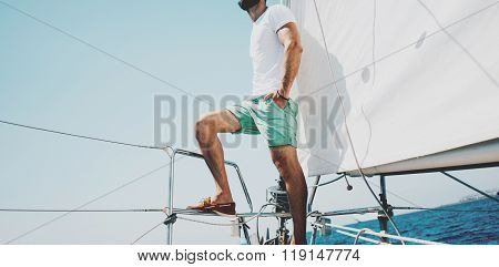 Low angle view of young bearded man standing on the yacht in sunny day. Horizontal mockup