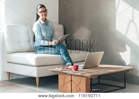 Multitasking. Beautiful young woman in glasses looking at camera with smile and working with touchpad while sitting on the couch in office