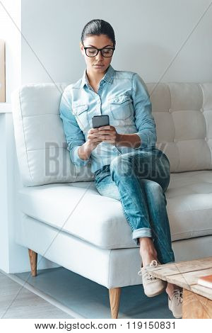 Making some changes in her timetable. Beautiful young woman in glasses using her smart phone while sitting on the couch in office