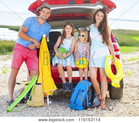 Portrait Of A Smiling Family With Two Children At Beach