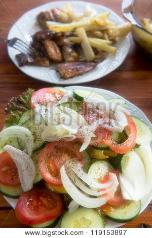 Fried potatoes, salad and fish - hake