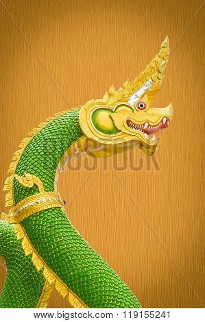 King of Nagas statue on grunge brown wooden wall
